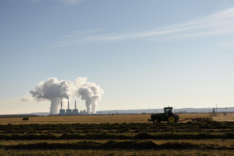 Emissions rising from a coal-fired power plant station smoke stacks with a tractor plowing a field in the foreground, near Wheatland, Wyoming.